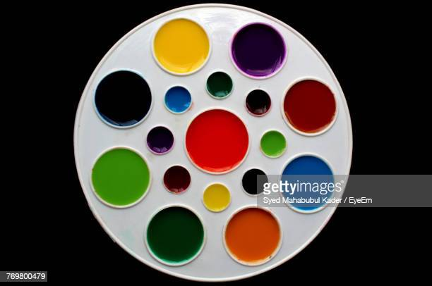 directly above shot of colorful palette on black background - artist's palette stock photos and pictures