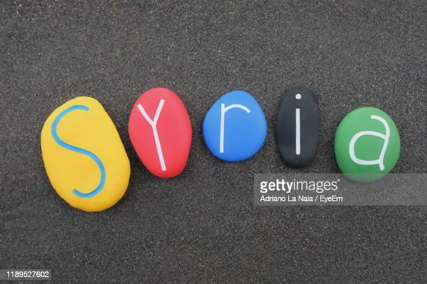 directly above shot of colorful pebbles with alphabets on table - syria stock pictures, royalty-free photos & images