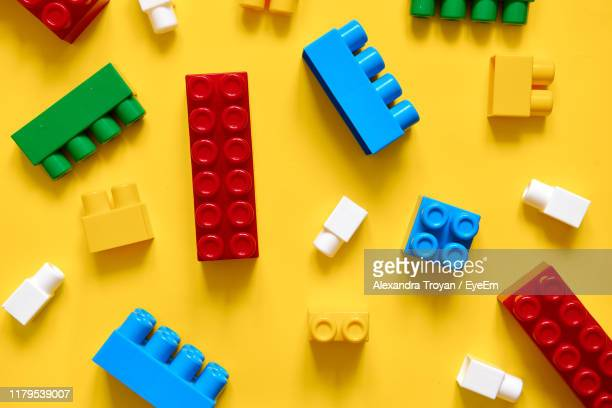 directly above shot of colorful toy blocks on yellow background - building blocks stock pictures, royalty-free photos & images