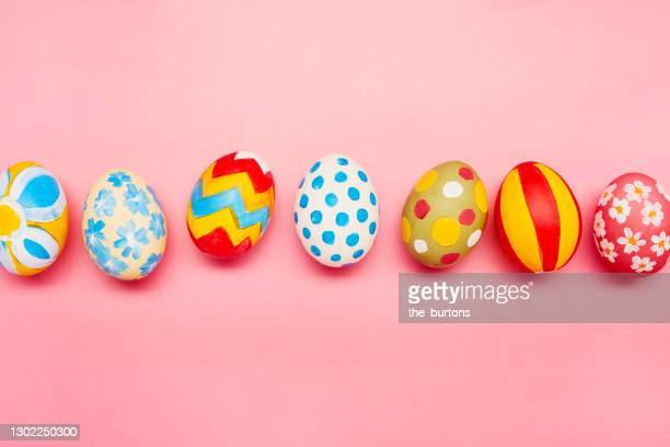 directly above shot of colourful painted easter eggs on pink background - easter egg stock pictures, royalty-free photos & images