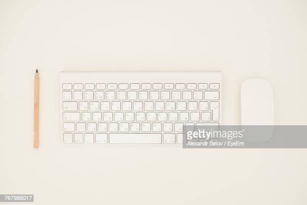Directly Above Shot Of Computer Keyboard With Mouse And Pencil Over White Background