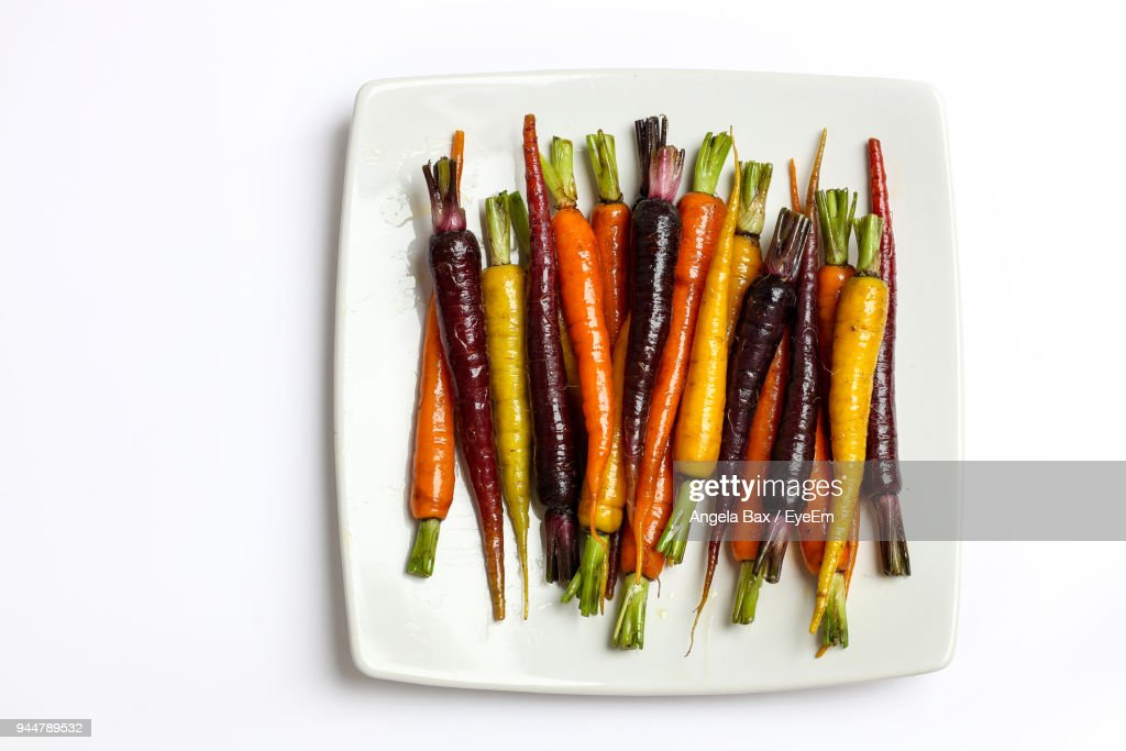 Directly Above Shot Of Cooked Carrots In Plate Over White Background : Stock Photo