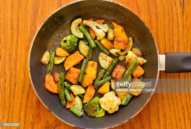 Directly Above Shot Of Cooked Vegetables In Frying Pan On Wooden Table