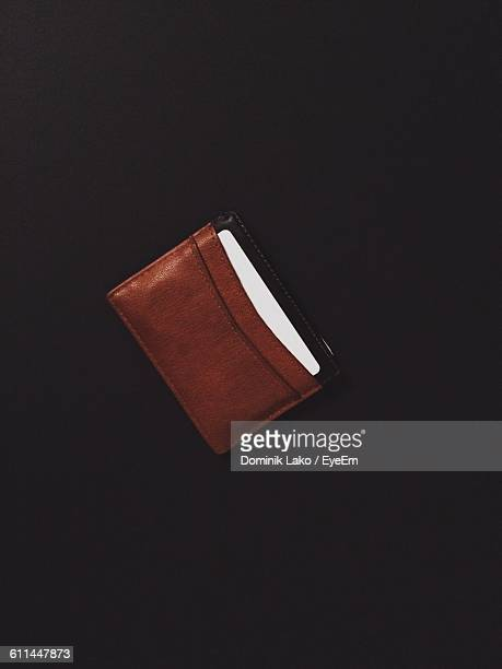 Directly Above Shot Of Credit Card In Leather Wallet On Black Background