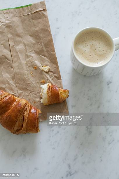 Directly Above Shot Of Croissant And Coffee Cup On Table