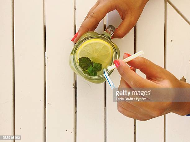Directly Above Shot Of Cropped Hand Holding Glass Of Lemon Juice On Table
