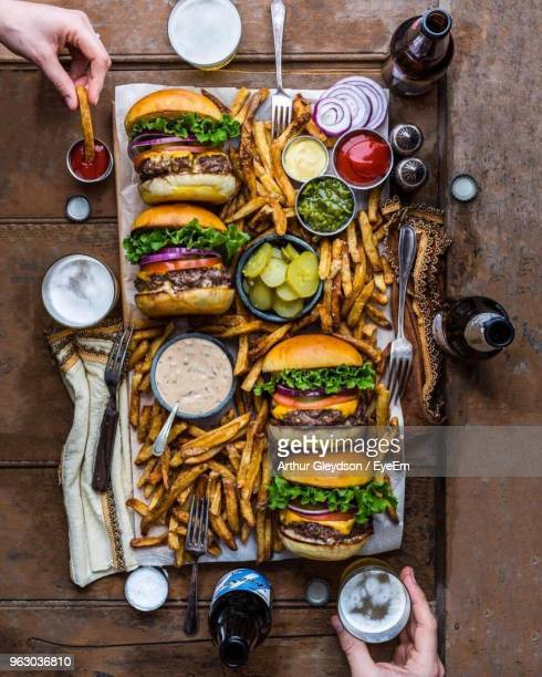 directly above shot of cropped hands having food at table - burger stock pictures, royalty-free photos & images