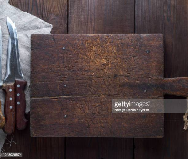 Directly Above Shot Of Cutting Board With Knives On Wooden Table