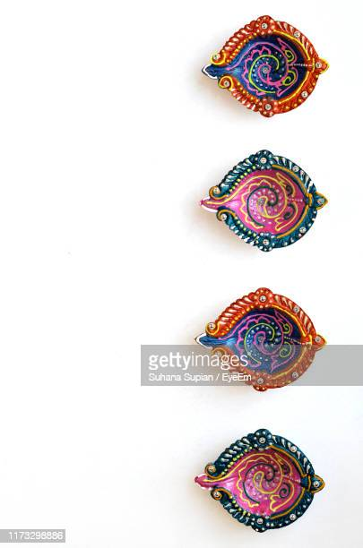 directly above shot of designed diyas on white background - diwali stock pictures, royalty-free photos & images