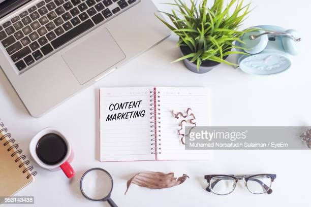 directly above shot of diary with content marketing text by various objects on table - 充足感 ストックフォトと画像