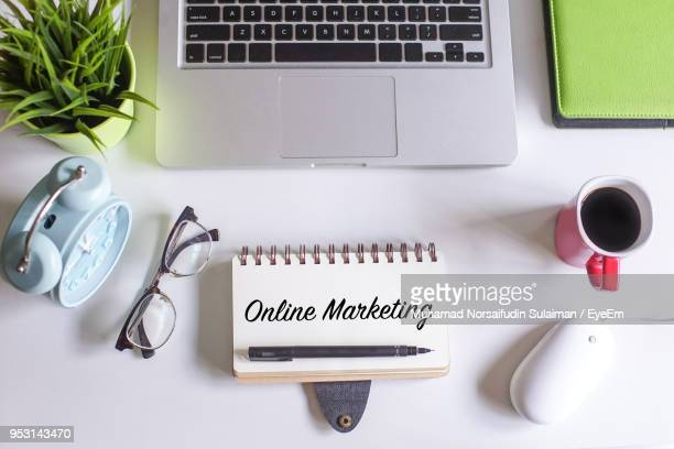 Directly Above Shot Of Diary With Online Marketing Text By Various Objects On Table