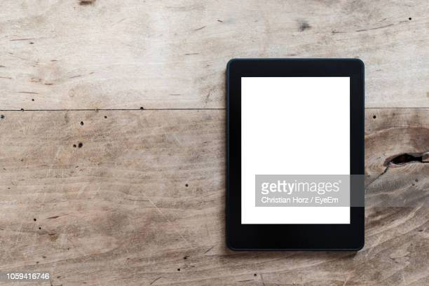 directly above shot of digital tablet on wooden table - e reader stock pictures, royalty-free photos & images