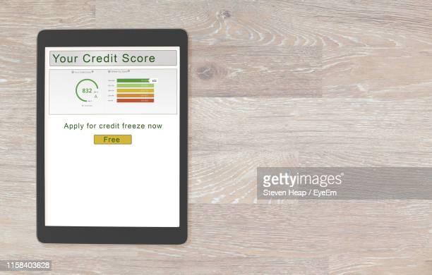 directly above shot of digital tablet with text on table - credit score stock pictures, royalty-free photos & images
