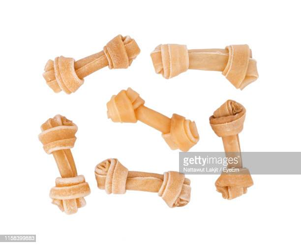 directly above shot of dog bones over white background - dog bone stock pictures, royalty-free photos & images