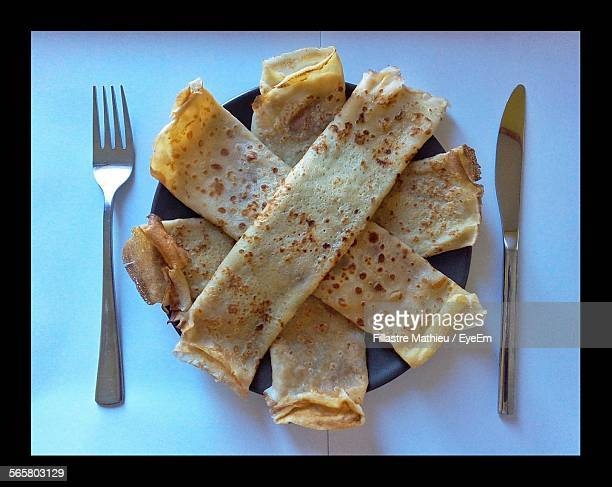 directly above shot of dosa on plate by fork and spoon - dosa stock photos and pictures