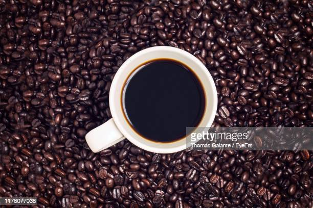 directly above shot of drink in cup amidst roasted coffee beans on table - coffee drink stock pictures, royalty-free photos & images
