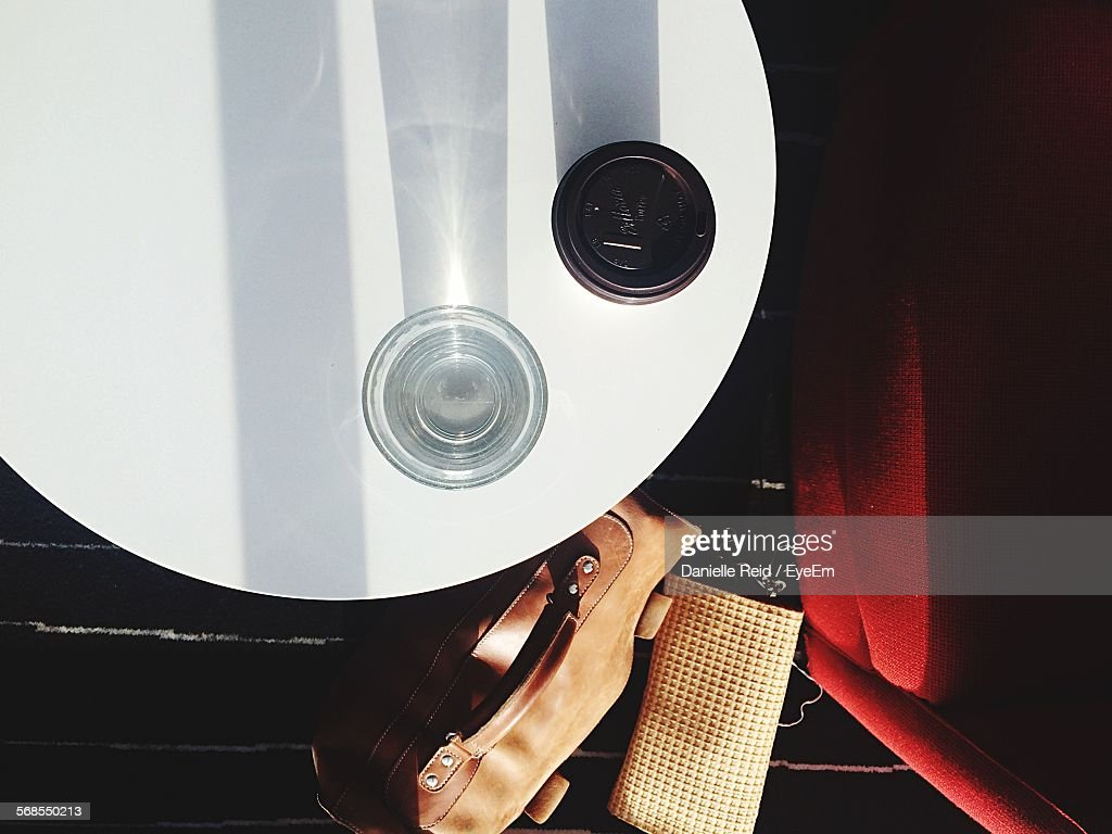 Directly Above Shot Of Drinking Glass On Table Beside Briefcase At Airport : Stock Photo