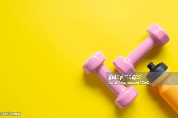 directly above shot of dumbbells and water bottle on yellow background - エクササイズ用具 ストックフォトと画像