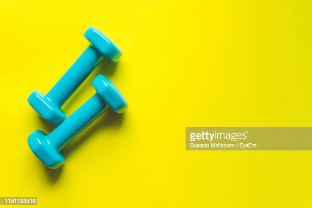 directly above shot of dumbbells on yellow background - weight stock pictures, royalty-free photos & images
