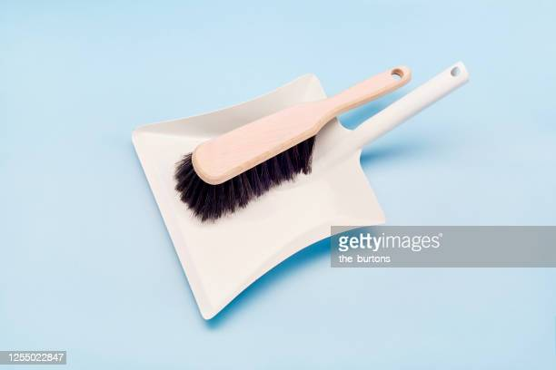 directly above shot of dustpan and broom on blue background - dustpan and brush stock pictures, royalty-free photos & images