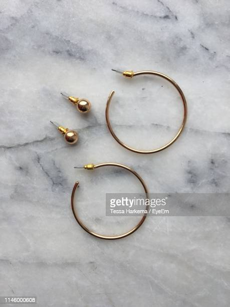 directly above shot of earrings on marble - earring stock pictures, royalty-free photos & images