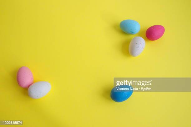 directly above shot of easter eggs against the yellow background - easter religious background stock pictures, royalty-free photos & images