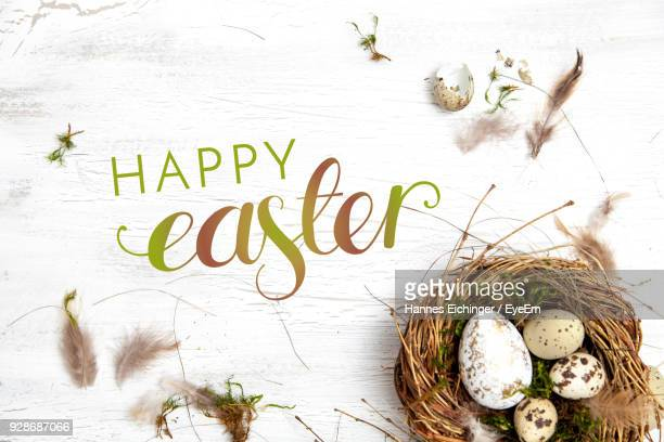 directly above shot of easter eggs by text in nest on wooden table - happy easter text stock pictures, royalty-free photos & images