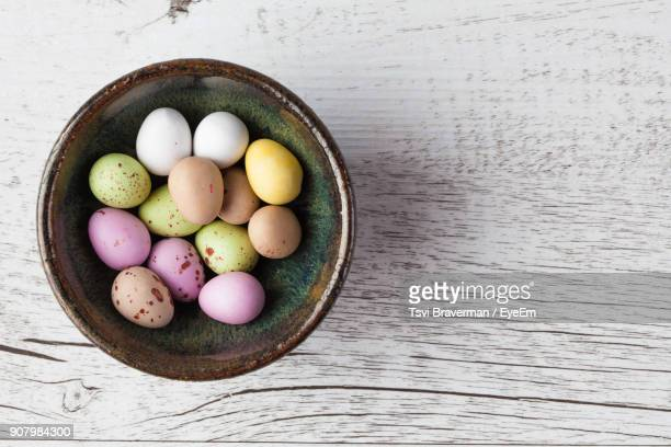 directly above shot of easter eggs in metallic bowl on wooden table - easter egg stock pictures, royalty-free photos & images