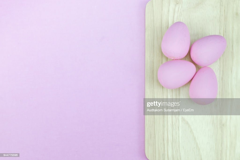 Directly Above Shot Of Easter Eggs On Cutting Board Over Pink Background : Stock Photo