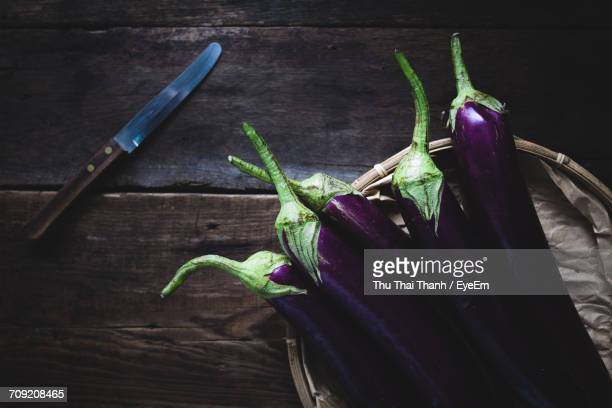 directly above shot of eggplants in basket by knife on wooden table - eggplant stock photos and pictures