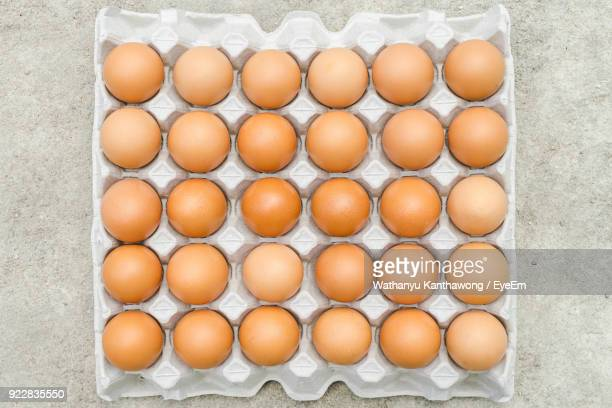 Directly Above Shot Of Eggs Arranged In Carton On Table