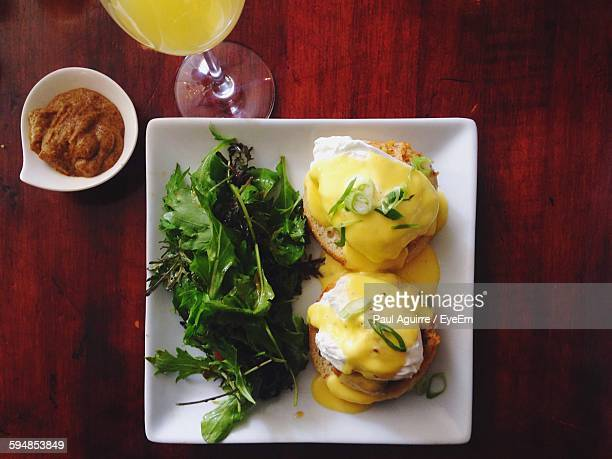 Directly Above Shot Of Eggs Benedict With Salad On Table