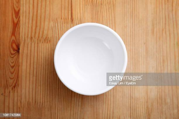 directly above shot of empty bowl on wooden table - bowl stock pictures, royalty-free photos & images
