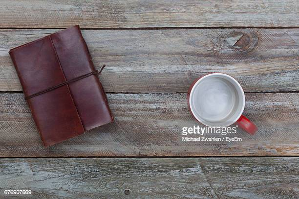 Directly Above Shot Of Empty Cup By Leather Dairy On Table