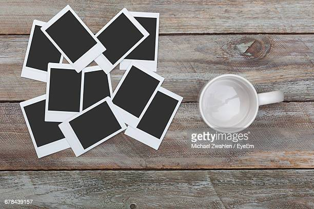 Directly Above Shot Of Empty Cup With Instant Print Transfers On Table