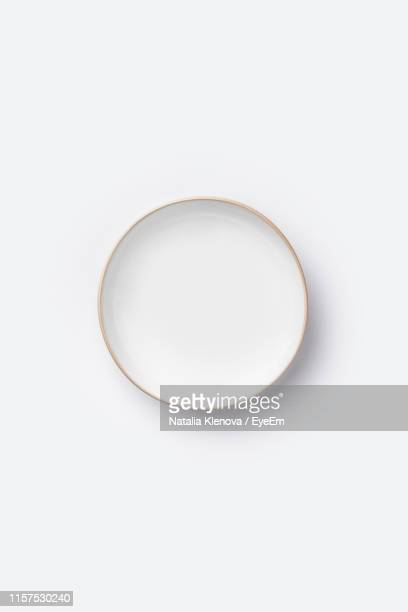 directly above shot of empty plate against white background - plate stock pictures, royalty-free photos & images