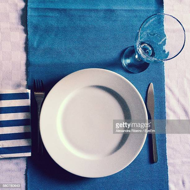 Directly Above Shot Of Empty Plate And Glass With Table Knife On Tablecloth