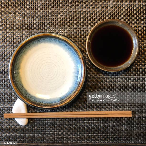 directly above shot of empty plate by chopsticks and condiment in bowl on table - soy sauce stock pictures, royalty-free photos & images