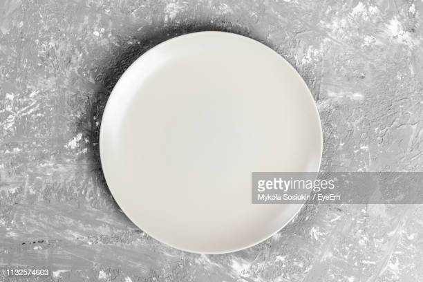 directly above shot of empty plate on gray table - plate stock pictures, royalty-free photos & images