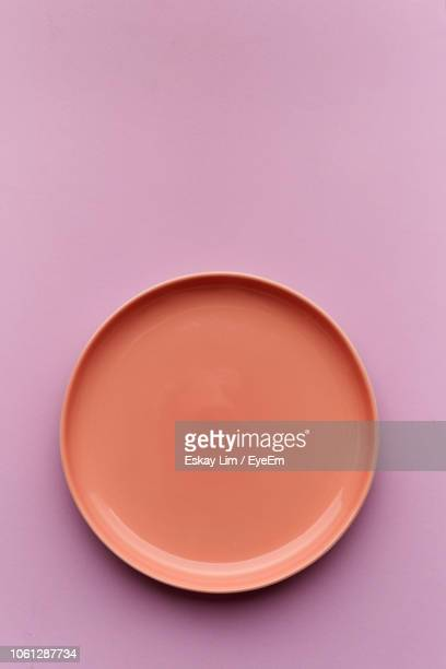 directly above shot of empty plate on purple background - plate stock pictures, royalty-free photos & images