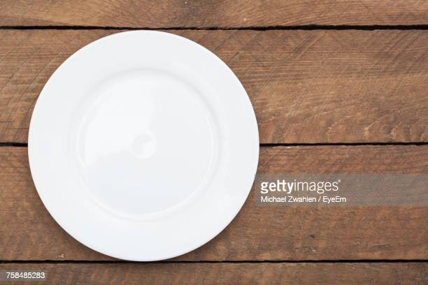 directly above shot of empty plate on wooden table - plate stock pictures, royalty-free photos & images