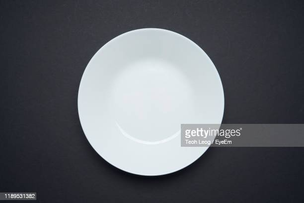 directly above shot of empty plate over black background - plate stock pictures, royalty-free photos & images