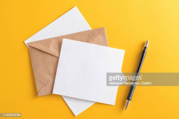 directly above shot of envelopes and pen on yellow background - four objects stock pictures, royalty-free photos & images