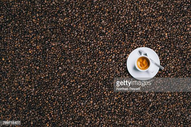 directly above shot of espresso cup on roasted coffee beans - large group of objects stock pictures, royalty-free photos & images