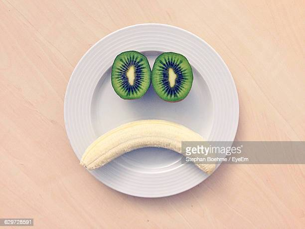 Directly Above Shot Of Face Made By Kiwi And Banana On Plate