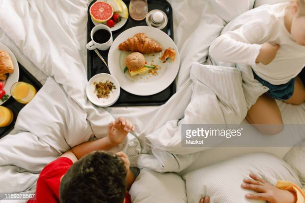 directly above shot of family having breakfast on bed in hotel - breakfast in bed stock pictures, royalty-free photos & images