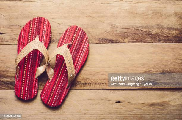 directly above shot of flip-flop on wooden floor - flip flops stock pictures, royalty-free photos & images