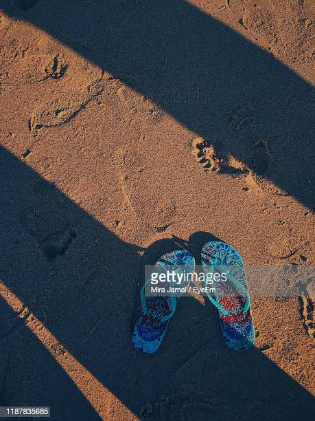 directly above shot of flip-flops on sand at beach - flip flop stock pictures, royalty-free photos & images