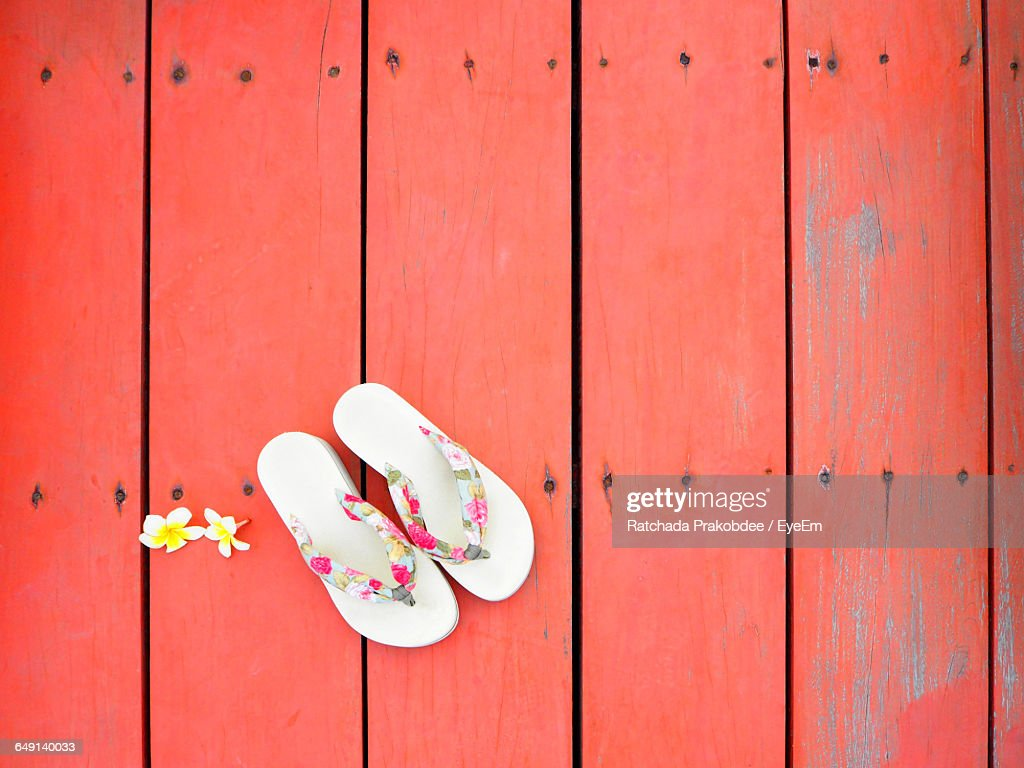 Directly Above Shot Of Flowers And Slippers On Red Floorboard : Stock Photo