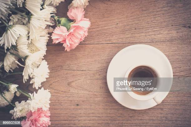 Directly Above Shot Of Flowers By Tea Cup On Table